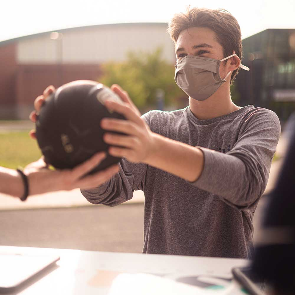 student handing volleyball to renter